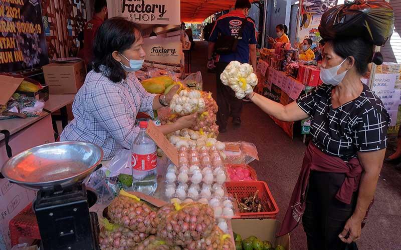 Pedagang melayani warga yang berbelanja saat pasar murah menjelang Hari Raya Idul Fitri 1442 Hijriah di Denpasar, Bali, Selasa (4/5/2021). Kegiatan yang digelar oleh Pemerintah Kota Denpasar pada 4-7 Mei 2021 tersebut untuk meringankan beban ekonomi masyarakat dalam memperoleh bahan pokok dengan harga yang lebih murah dari harga di pasaran. ANTARA FOTO/Nyoman Hendra Wibowo