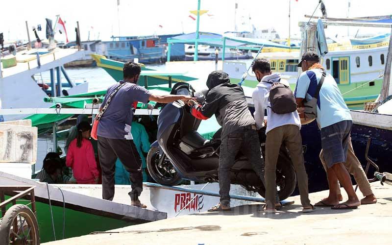 Warga kepulauan Kabupaten Pangkep mulai mudik dengan mengangkut sepeda motor melalui Pelabuhan Paotere, Makassar, Sulawesi Selatan, Selasa (4/5/2021). Sejumlah warga memilik mudik lebih awal guna menghindari larangan mudik pemerintah yang akan berlaku Kamis (6/5). Bisnis/Paulus Tandi Bone