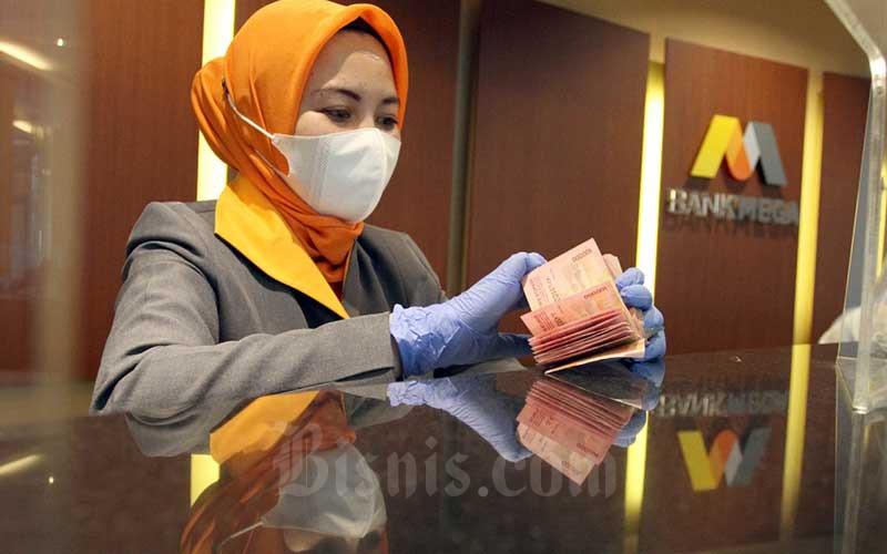 Karyawan menghitung uang di Bank Mega Makassar, Sulawesi Selatan, Selasa (4/5/2021). PT Bank Mega Tbk. mencetak laba bersih sebesar Rp747,24 miliar per 31 Maret 2021. Laba tersebut tumbuh 11,63 persen dibandingkan dengan laba periode yang sama tahun lalu sebesar Rp669,39 miliar. Bisnis/Paulus Tandi Bone