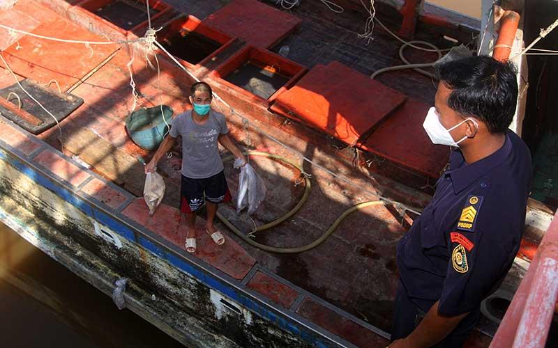 Seorang petugas menyaksikan nelayan memperlihatkan ikan hasil tangkapan kapal ikan asing berbendera Vietnam dengan nomor lambung KG 5090 TS di dermaga Stasiun Pengawasan Sumber Daya Kelautan dan Perikanan (PSDKP) Pontianak di Kabupaten Kubu Raya, Kalimantan Barat, Selasa (4/5/2021). Kapal Pengawas Perikanan Hiu 17 Kementerian Kelautan dan Perikanan menangkap satu kapal ikan asing ilegal berbendera Vietnam KG 5090 TS beserta tiga awak kapal di Laut Natuna Utara pada Selasa (27/4/2021), yang selanjutnya digiring ke Stasiun PSDKP Pontianak untuk proses hukum lebih lanjut. ANTARA FOTO/Jessica Helena Wuysang