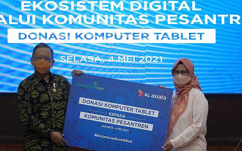 Menteri Koordinator Bidang Politik, Hukum, dan Keamanan Republik Indonesia, Mohammad Mahfud MD (kiri) bersama dengan Presiden Direktur & CEO XL Axiata, Dian Siswarini (kanan) dalam acara penyerahan donasi laptop kepada pesantren di Jakarta, Selasa (4/5/2021). Bisnis
