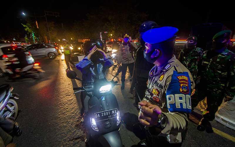 Petugas gabungan menyiapkan pembatas jalan saat uji coba pembatasan arus masuk di Jalan Ahmad Yani Km 6, Banjarmasin, Kalimantan Selatan, Rabu (5/5/2021) malam.  Kepolisian Resor Kota Banjarmasin bersama TNI, Sat Pol PP dan Dinas Perhubungan melakukan uji coba pembatasan arus masuk di malam hari di Kota Banjarmasin guna mencegah mobilitas masyarakat saat pemberlakuan jam malam nanti. ANTARA FOTO/Bayu Pratama S