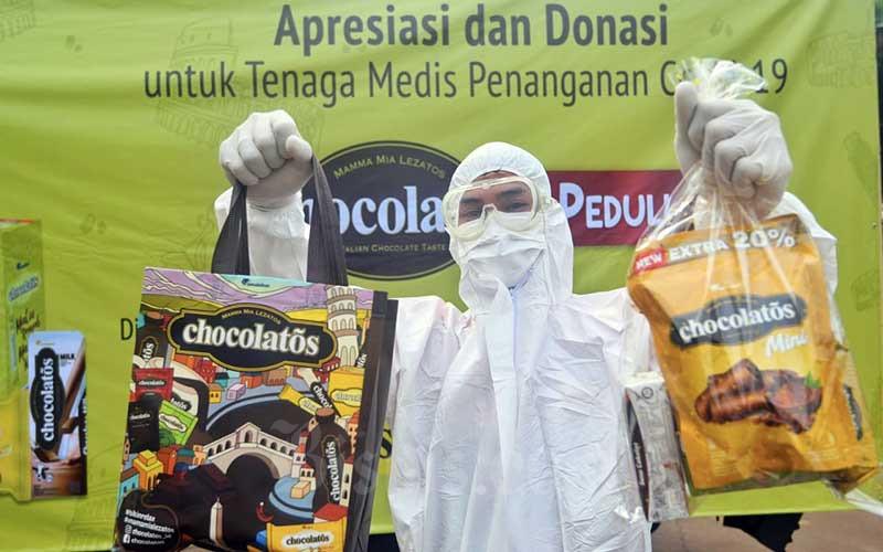 Tenaga kesehatan menunjukan paket bantuan dari GarudaFood di Jakarta, Kamis (6/5/2021). Melalui kegiatan Chocolatos Peduli, GarudaFood menyerahkan donasi lebih dari 2.600 paket produk yang terdiri dari 13.000 produk Chocolatos dan juga makanan siap saji. Kegiatan ini diharapkan dapat menciptakan momen keceriaan dan kenikmatan cokelat Italia yang berlimpah untuk semua dedikasi yang diberikan oleh tenaga kesehatan dalam berjuang melawan Covid-19. Bisnis/Abdurachman