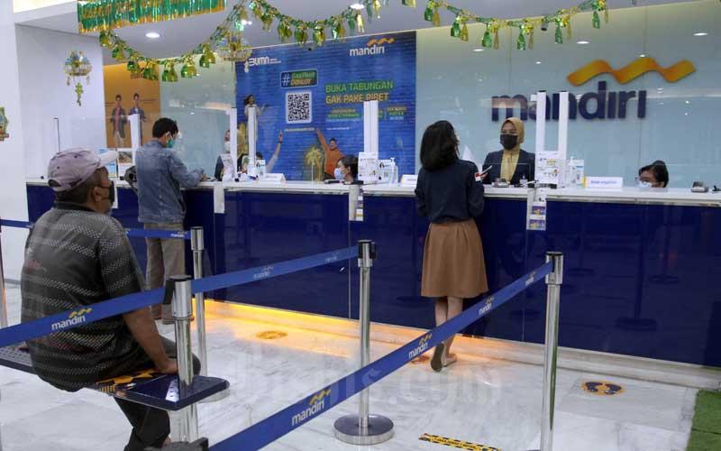 Nasabah melakukan transaksi perbankan di Bank Mandiri Makassar, Sulawesi Selatan, Kamis (5/5/2021). PT. Bank Mandiri Tbk. Wilayah X Makassar berhasil mencatatkan pertumbuhan kredit sebesar 19,2 persen secara year on year pada kuartal I/2021. Pertumbuhan tersebut didorong oleh meningkatnya penyaluran kredit wholesale (korporasi) sebesar 104,7 persen yoy. Bisnis/Paulus Tandi Bone
