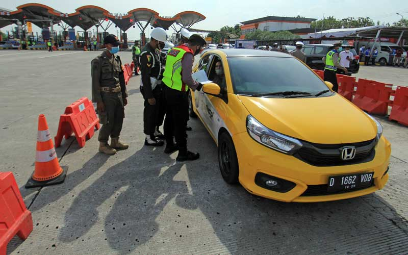 Personel Kepolisian memeriksa kelengkapan surat dan KTP saat penyekatan larangan mudik lebaran di Gerbang Tol Cipali, Palimanan, Cirebon, Jawa Barat, Kamis (6/5/2021). Pemeriksaan tersebut sebagai upaya untuk menyekat masyarakat yang nekat mudik jelang perayaan Hari Raya Idul Fitri 1442 H dari arah Jakarta menuju Jawa Tengah. ANTARA FOTO/Dedhez Anggara