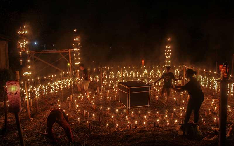 Warga menyalakan lentera yang digantung pada 'Lampu Colok' berbentuk miniatur bangunan Kabah dalam Festival Lampu Colok di Pekanbaru, Riau, Sabtu (8/5/2021). Festival lampu colok ini digelar pada malam ke 27 Ramadan hingga malam terakhir Ramadan. ANTARA FOTO/Rony Muharrman