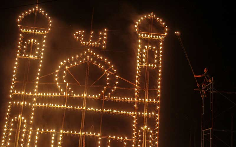 Warga menyalakan lentera yang digantung pada 'Lampu Colok' berbentuk miniatur masjid dalam Festival Lampu Colok di Pekanbaru, Riau, Sabtu (8/5/2021) malam. Festival lampu colok ini digelar pada malam ke 27 Ramadan hingga malam terakhir Ramadan. ANTARA FOTO/Rony Muharrman