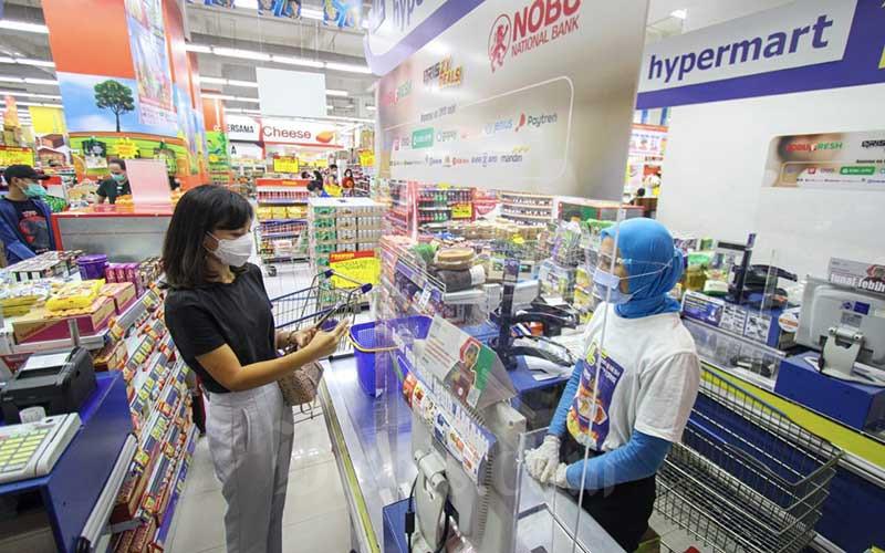 Nasabah melakukan pembayaran menggunakan metode Quick Response Code Indonesian Standard (QRIS) Nobu Bank saat berbelanja di salah satu gerai Hypermart di Jakarta, Minggu (9/5/2021). PT Bank Nationalnobu Tbk. (Nobu Bank) terus mengadakan berbagai promo sebagai bentuk sosialisasi penggunaan QRIS, di antaranya program Kejutan Berkah Idul Fitri yang berlangsung 7-12 Mei 2021 di seluruh gerai Hypermart, Foodmart, Primo, Hyfresh, Boston dan Foodmart Express. Hingga 1 tahun mendatang, Nobu Bank memproyeksikan frekuensi transaksi digital melalui QRIS dapat mencapai lebih dari 1 juta transaksi per bulan. Bisnis/Arief Hermawan P