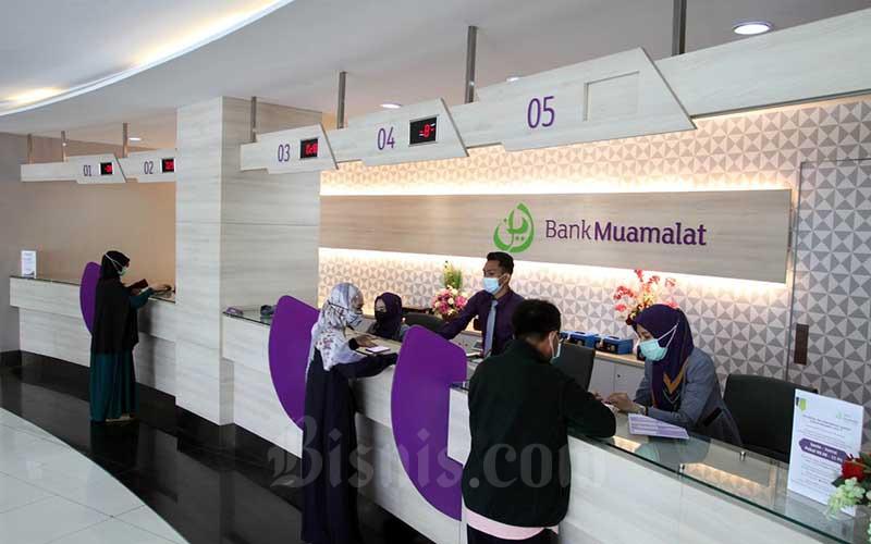 Nasabah melakukan transaksi di Bank Muamalat Makassar, Sulawesi Selatan, Senin (10/5/2021). Potensi pengembangan pendapatan berbasis komisi atau fee based income (FBI) perbankan syariah tahun diperkirakan masih berlanjut. Berdasarkan data Otoritas Jasa Keuangan (OJK), pendapatan dari penyertaan, fee, komisi, provisi akhir tahun lalu tercatat Rp2,8 triliun, naik 12, 22 persen secara tahunan. Bisnis/Paulus Tandi Bone