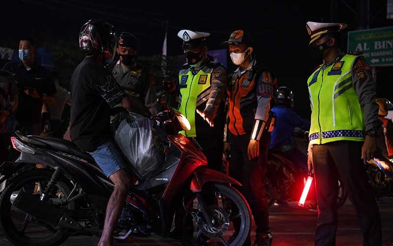 Petugas kepolisian menghentikan kendaraan saat melintasi posko penyekatan mudik di Kedungwaringin, Kabupaten Bekasi, Jawa Barat, Senin (10/5/2021). Polda Metro Jaya menambah jumlah petugas guna mengecek ribuan pemudik yang melintasi pos penyekatan perbatasan Bekasi -Karawang, Jawa Barat. ANTARA FOTO/Wahyu Putro A
