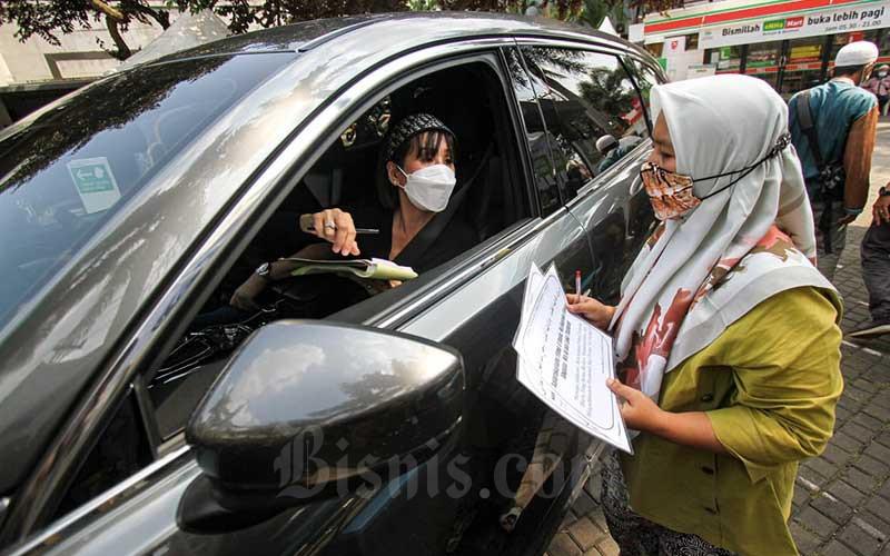 Umat muslim melakukan pembayaran zakat fitrah di Gerai Zakat Infak dan Shodaqoh Drive Thru di Masjid Raya Nurul Hidayah, Tanah Kusir, Jakarta, Selasa (11/5/2021). Layanan pembayaran zakat tersebut seluruh prosesnya dilakukan tanpa turun dari kendaraan, yang bertujuan untuk memberikan kemudahan bagi muzakki dalam membayar zakat, serta menghindari kontak fisik di tengah pandemi Covid-19. Bisnis/Arief Hermawan P