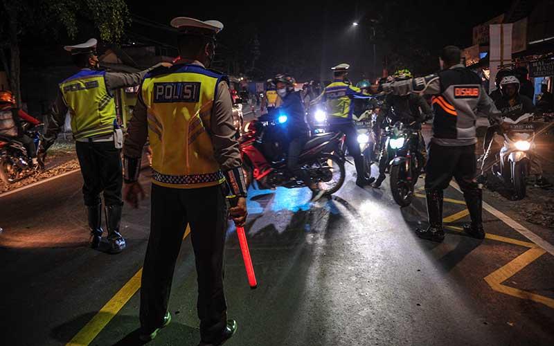 Petugas Kepolisian memutarbalikan kendaraan roda dua di posko penyakatan mudik Limbangan, Kabupaten Garut, Jawa Barat, Selasa (11/5/2021). Pada H-2 Idul Fitri 1442 H, petugas di posko penyekatan mudik Limbangan memutarbalikan ratusan pengendara roda dua yang hendak mudik ke arah Tasikmalaya, Ciamis dan Jawa Tengah. ANTARA FOTO/Raisan Al Farisi