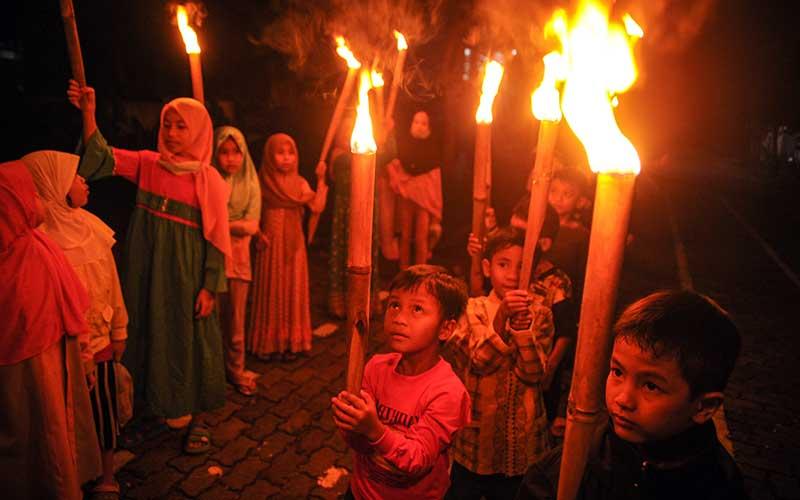 Sejumlah anak mengikuti pawai obor di Komplek Grand Cinunuk Indah, Kabupaten Bandung, Jawa Barat, Rabu (12/5/2021). Pawai obor yang diselenggarakan oleh pengurus DKM Masjid setempat tersebut ditujukan untuk menyambut Idul Fitri 1442 H yang ditetapkan oleh pemerintah pada Kamis (13/5/2021). ANTARA FOTO/Raisan Al Farisi