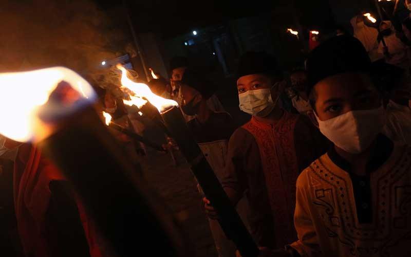 Sejumlah santri TPQ Pesantren Miftahul Huda membawa obor sambil bertakbir berkeliling desa di Blitar, Jawa Timur, Rabu (12/5/2021) malam. Tradisi takbiran keliling yang dilakukan dengan penerapan ptotokol kesehatan ketat guna menghindari penularan Covid-19 tersebut guna menyambut hari raya Idul Fitri 1442 H . ANTARA FOTO/Irfan Anshori