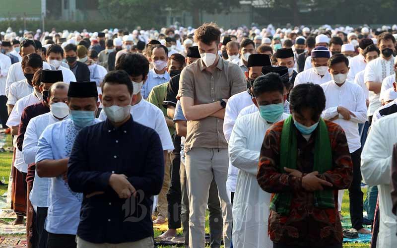 Umat muslim melaksanakan Salat Idulfitri di Halaman Masjid Al-Azhar, Jakarta, Kamis (13/5/2021). Pelaksanaan Salat Idulfitri 1442 H di sejumlah daerah dilakukan berjamaah di masjid dan lapangan dengan tetap menerapkan protokol kesehatan seperti mengenakan masker dan menjaga jarak. Bisnis/Eusebio Chrysnamurti