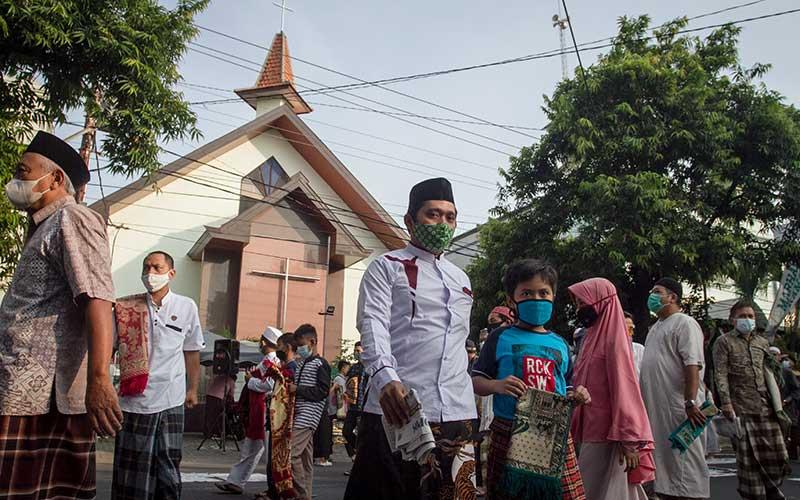 Umat muslim melaksanakan Shalat Idul Fitri 1442 H di Masjid Al Hikmah yang bersebelahan dengan Gereja Kristen Jawa (GKJ) Joyodiningratan, Kratonan, Serengan, Solo, Jawa Tengah, Kamis (13/5/2021). Sebagai bentuk tolaransi umat beragama, Gereja setempat memindahkan jadwal kebaktian Kenaikan Isa Almasih dari pagi menjadi sore hari untuk menghormati umat Islam yang melaksanakan salat Ied. ANTARA FOTO/Mohammad Ayudha