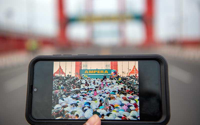 Foto kolase perbandingan suasana Shalat Idul Fitri 1440 H di Jembatan Ampera Palembang, Sumatera Selatan, sebelum adanya pandemi COVID-19 (kiri) dan saat pandemi (kanan), Kamis (13/5/2021).  Pemerintah Kota Palembang bersama Kemenag Palembang, Polrestabes dan Kodim 0418/Palembang melarang warga untuk melaksanakan Shalat Idul Fitri 1442 H di masjid secara menyeluruh dan menganulir izin shalat berdasarkan zonasi kelurahan sebelumnya. ANTARA FOTO/Nova Wahyudi