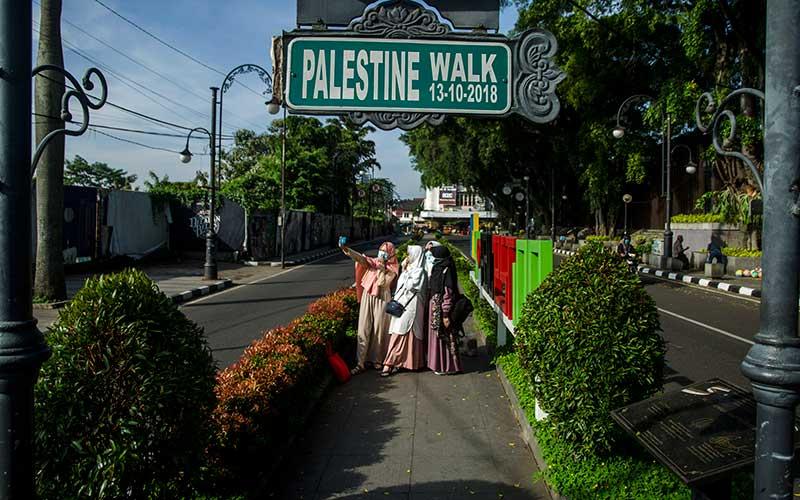 Warga berswafoto di Pedestrian Palestine Walk kawasan Asia Afrika, Bandung, Jawa Barat, Kamis (13/5/2021).  Warga Kota Bandung menikmati suasana sepi di sejumlah titik wisata kota usai melaksanakan Shalat Ied 1442 Hijriah. ANTARA FOTO/Novrian Arbi
