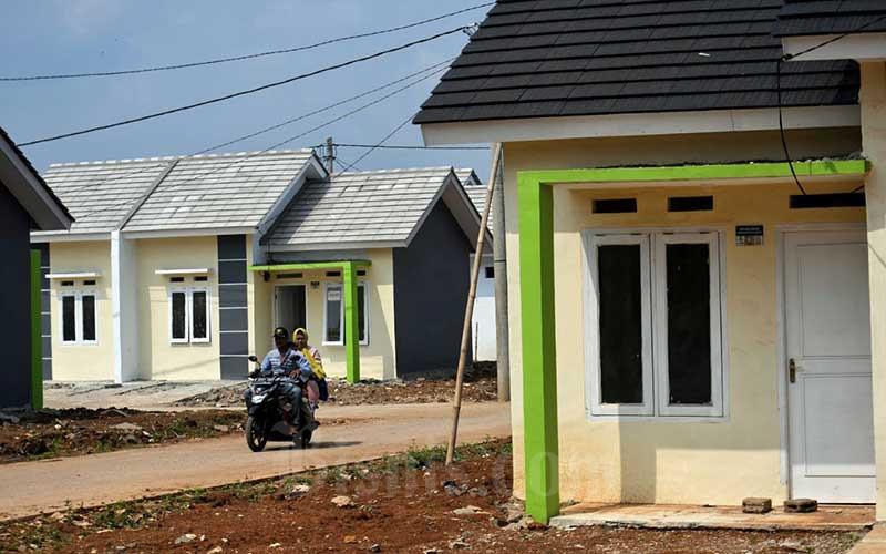 Warga melintas di proyek pembangunan rumah subsidi di Bogor, Minggu (16/5/2021). Pemberian insentif Pajak Pertambahan Nilai (PPN) sejak 1 Maret 2021 berdampak positif bagi penjualan rumah siap huni di Jabodebek dan Banten, menurut hasil riset Indonesia Property Watch (IPW) penjualan meningkat hingga 661 persen selama kuartal I/2021. Bisnis/Abdurachman