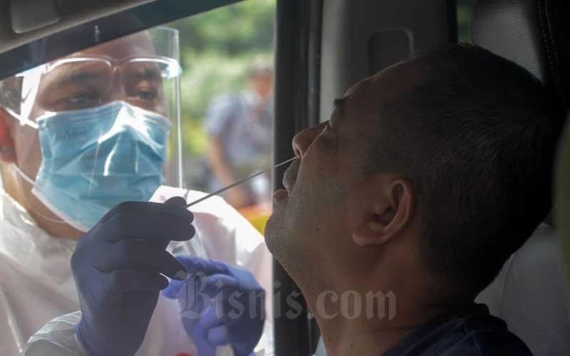 Petugas melakukan pemeriksaan tes usap antigen Covid-19 pada pengendara arus balik lebaran di Tol Jakarta Cikampek KM 34B, Cikarang, Jawa Barat, Minggu (16/5/2021). Direktorat Lalu Lintas (Ditlantas) Polda Metro Jaya dan sejumlah instansi terkait melakukan tesantigensecara gratis bagi pengendara yang belum memiliki surat bebascovid-19 untuk kembali ke wilayah Jakarta dan sekitarnya. Total terdapat 109 titik posko untuk melaksanakan tes acak di sejumlah perbatasan memasuki ibukota. Bisnis/Himawan L Nugraha