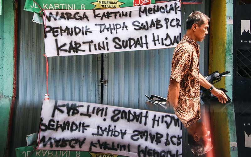 Warga melintas di dekat spanduk peringatan untuk pemudik di kawasan Sawah Besar, Jakarta, Minggu (16/5/2021). Spanduk tersebut untuk memperingati warga yang kembali dari mudik agar membawa surat bebas Covid-19. ANTARA FOTO/Rivan Awal Lingga
