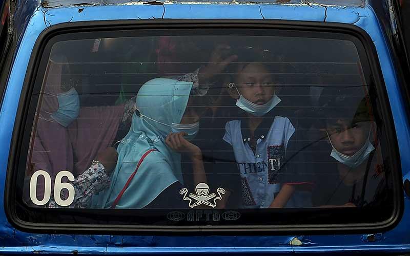 Warga berada di dalam angkot yang melintas Jalan Margonda Raya, Depok, Jawa Barat, Minggu (16/5/2021). Kementerian Perhubungan memprediksi puncak arus mudik lokal di wilayah aglomerasi terjadi pada 16 Mei 2021. ANTARA FOTO/Sigid Kurniawan