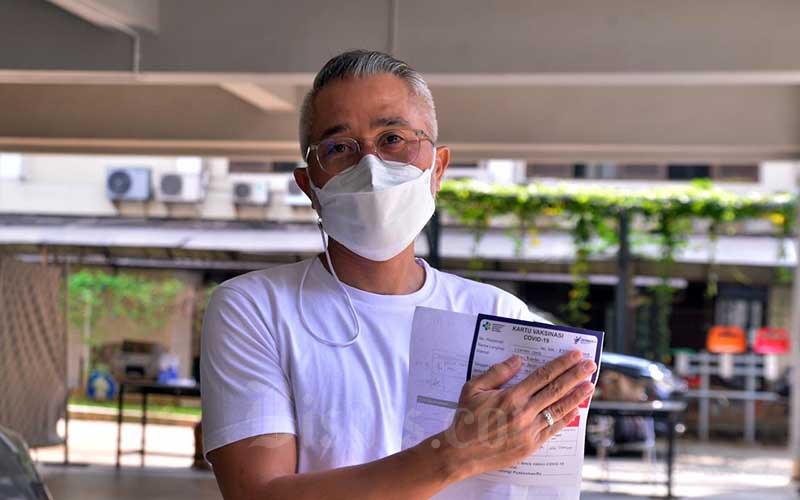 Aktor Lukman Sardi menunjukkan sertifikat vaksin usai melakukan vaksinasi Covid-19 dosis kedua di Gereja Kristen Indonesia (GKI) Pondok Indah, Jakarta, Senin (17/5/2021). Vaksinasi Covid-19 diberikan kepada 120 orang secara drive thru. Vaksinasi ini dilakukan untuk mempercepat pemulihan sektor ekonomi kreatif di Tanah Air. Bisnis/Fanny Kusumawardhani