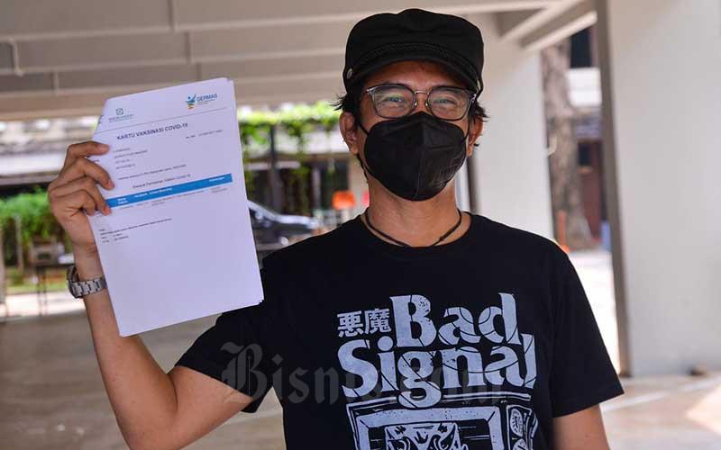 Musisi Piyu 'Padi' menunjukkan sertifikat vaksin usai melakukan vaksinasi Covid-19 dosis kedua di Gereja Kristen Indonesia (GKI) Pondok Indah, Jakarta, Senin (17/5/2021). Vaksinasi Covid-19 diberikan kepada 120 orang secara drive thru. Vaksinasi ini dilakukan untuk mempercepat pemulihan sektor ekonomi kreatif di Tanah Air. Bisnis/Fanny Kusumawardhani