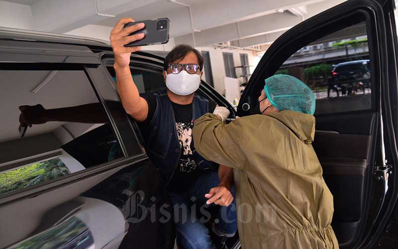 Komika Soleh Solihun melakukan vaksinasi Covid-19 dosis kedua di GKI Pondok Indah, Jakarta, Senin (17/5/2021). Vaksinasi Covid-19 tersebut diberikan kepada 120 orang secara drive thru. Vaksinasi ini dilakukan untuk mempercepat pemulihan sektor ekonomi kreatif di Tanah Air. Bisnis/Fanny Kusumawardhani