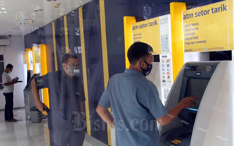 Nasabah menaik uang tunai di Anjungan Tunai Mandiri (ATM) Bank Mandiri di Makassar, Sulawesi Selatan, Senin (17/5/2021). PT Bank Mandiri (Persero) Tbk. mengklaim konsumsi masyarakat makin membaik pada lebaran tahun ini. Perseroan mencatat  realisasi penarikan uang tunai berdasarkan net kebutuhan pada musim libur lebaran tahun ini adalah sekitar Rp22,2 triliun. Bisnis/Paulus Tandi Bone