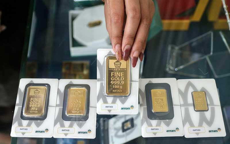 Karyawan menunjukan replika emas logam mulia di Butik Antam, Jakarta, Senin (17/5/2021). Harga emas batangan PT Aneka Tambang Tbk. (Antam) pada Senin (17/5/2021) berada di posisi lebih tinggi dibanding hari kemarin. Berdasarkan informasi dari Unit Bisnis Pengolahan dan Pemurnian Logam Mulia Antam, harga dasar emas 24 karat ukuran 1 gram dijual senilai Rp937.000, naik Rp4.000 per gram dari harga sebelumnya. Begitu pula untuk emas satuan terkecil dengan ukuran 0,5 gram dijual Rp518.500, naik Rp2.000 daripada harga sebelumnya. Bisnis/Eusebio Chrysnamurti
