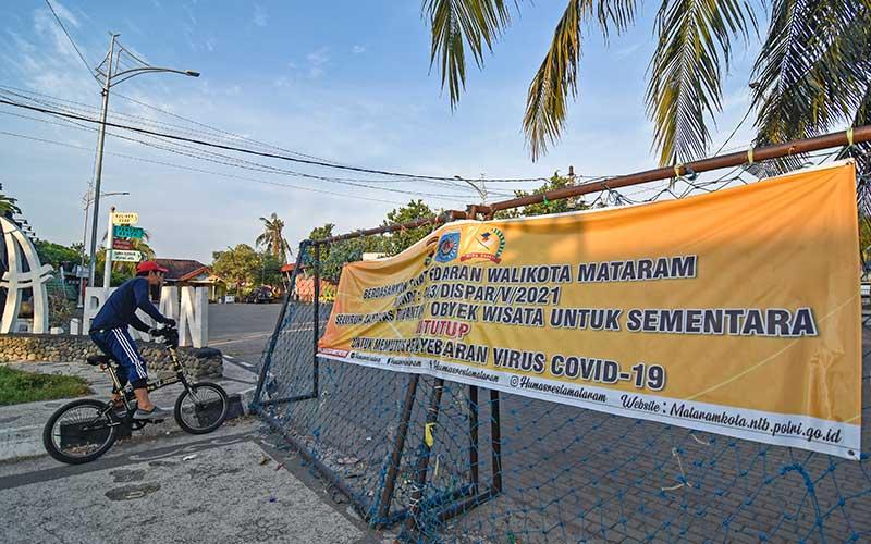 """Seorang pria memasuki gerbang obyek wisata pantai Ampenan yang ditutup di Ampenan, Mataram, NTB, Rabu (19/5/2021). Pemerintah Kota Mataram menutup semua destinasi wisata pantai yang biasanya ramai dikunjungi warga saat merayakan tradisi """"Lebaran Topat"""" di Lombok hingga 20 Mei 2021 untuk mengantisipasi terjadinya kerumunan dan mencegah penyebaran Covid-19, ANTARA FOTO/Ahmad Subaidi"""