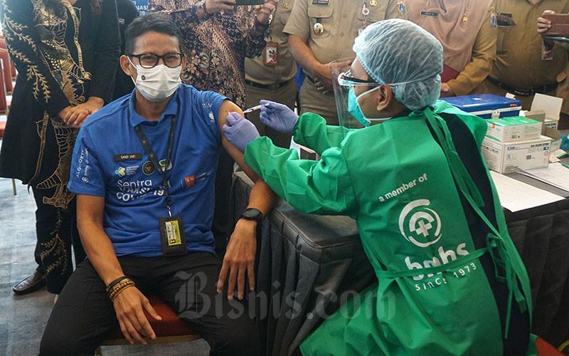 Menteri Pariwisata dan Ekonomi Kreatif Sandiaga Salahuddin Uno menerima vaksin di Sentra Vaksin di D'Capital Neo Soho, Selasa (8/6/2021). Danone Indonesia bersama para partner Alodokter, Neo Soho, dan RS Bunda memfasilitasi penyediaan sarana prasarana pada Sentra Vaksin Covid-19 di D'Capital Neo Soho. Danone Indonesia telah melakukan berbagai upaya kemitraan dalam mencegah Covid-19 melalui dukungan penyediaan alat pelindung diri seperti sarung tangan, masker, baju hazmat, dan hand sanitizer bagi ratusan tenaga kesehatan yang bertugas, pemberian edukasi nutrisi kepada para lansia, serta pemenuhan kebutuhan hidrasi peserta vaksin dan tenaga kesehatan melalui produk AQUA. Bisnis/Suselo Jati