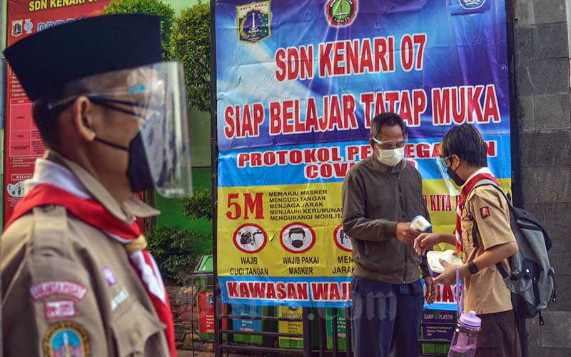 Guru memeriksa suhu tubuh siswa di SDN Kenari 07/08, Jakarta, Rabu (9/6/2021). Pemerintah Provinsi DKI Jakarta memulai uji coba tahap kedua sekolah tatap muka pada hari ini (9/7). Pelaksanaan uji coba sekolah tatap muka tahap kedua ini berlangsung selama tiga minggu hingga 26 Juni 2021 mendatang.Kasubag Dinas Pendidikan DKI Jakarta Taga Radja Gah mengatakan, tercatat 226 sekolah di wilayah Jakarta yang akan mengikuti pembelajaran tatap muka secara terbatas. Bisnis/Fanny Kusumawardhani