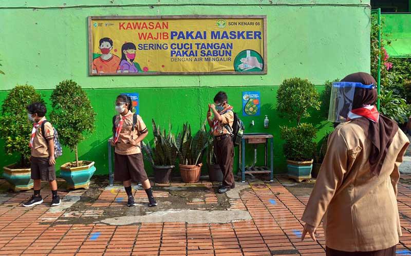 Siswa menanti dijemput orang tua usai uji coba pembelajaran tatap muka tahap dua di SDN Kenari 07/08, Jakarta, Rabu (9/6/2021). Pemerintah Provinsi DKI Jakarta memulai uji coba tahap kedua sekolah tatap muka pada hari ini (9/7). Pelaksanaan uji coba sekolah tatap muka tahap kedua ini berlangsung selama tiga minggu hingga 26 Juni 2021 mendatang.Kasubag Dinas Pendidikan DKI Jakarta Taga Radja Gah mengatakan, tercatat 226 sekolah di wilayah Jakarta yang akan mengikuti pembelajaran tatap muka secara terbatas. Bisnis/Fanny Kusumawardhani