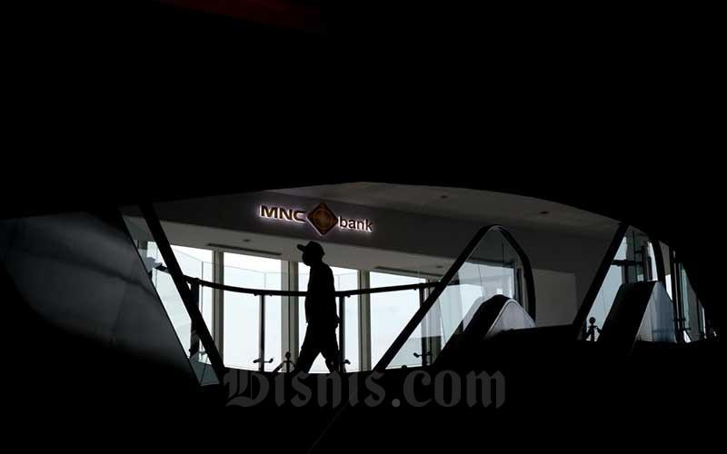 Karyawan melintas di dekat logo milik PT Bank MNC Internasional Tbk. di Jakarta, Rabu (9/6/2021). Pemegang saham menyetujui rencana Penambahan Modal Perseroan Tanpa Hak Memesan Efek Terlebih Dahulu (Non HMETD) dan rencana Penambahan Modal Dengan Hak Memesan Efek Terlebih Dahulu (HMETD) dalam RUPSLB hari ini. Dana yang diperoleh dari dua aksi korporasi tersebut akan digunakan untuk memperkuat struktur permodalan MNC Bank, memperluas kapasitas pinjaman MNC Bank dan akuisisi nasabah secara digital untuk mendukung pertumbuhan bisnis. Bisnis/Nurul Hidayat