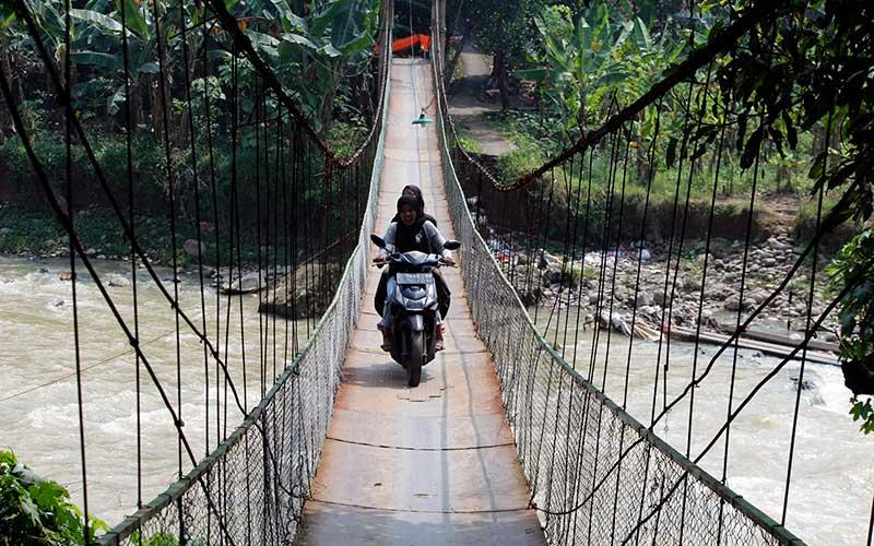 Pengendara motor melintas di jembatan gantung Kantalarang di atas Sungai Cikaniki, Kabupaten Bogor, Jawa Barat, Rabu (9/6/2021). Jembatan gantung sepanjang 100 meter yang sempat terputus akibat banjir bandang pada tahun 2020 tersebut telah selesai diperbaiki oleh dana swadaya masyarakat dan menjadi akses utama bagi warga Kampung Tonjong, Desa Karehkel, Kecamatan Rumpin dan Kampung Kantalarang, Desa Leuwibatu, Kecamatan Leuwiliang. ANTARA FOTO/Arif Firmansyah