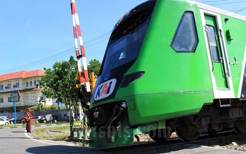 Seorang siswi tengah menunggu kereta api Minangkabau Ekspres melintasi di pelintasan sebidang di Jalan Adinegoro, Lubuk Buaya, Kota Padang, Sumatra Barat, Kamis (10/6/2021). PT Kereta Api Indonesia (KAI) menyatakan jumlah pelintasan sebidang secara nasional mencapai 4.680 dengan mayoritas 73 persen pelintasan di antaranya tidak dijaga. Pelintasan sebidang yang paling banyak tersebar di wilayah Daop 8 dengan jumlah 559 pelintasan, dengan jumlah yang tidak dijaga terbanyak mencapai 305 pelintasan.Bisnis/Noli