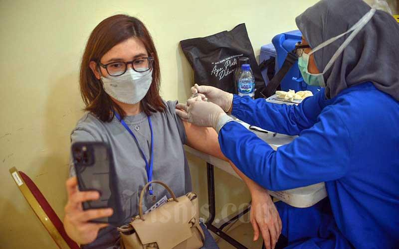 Tenaga kesehatan menyuntikan vaksin Covid-19 kepada warga di GOR Pangadegan, Jakarata, Kamis (10/6/2021). Kementerian Kesehatan memulai program vaksinasi Covid-19 tahap ketiga yang menyasar sekitar 4,8 juta penduduk wilayah DKI Jakarta pada kelompok usia minimal 18 tahun. Vaksinasi tersebut ditargetkan rampung pada Desember 2021. Bisnis/Fanny Kusumawardhani