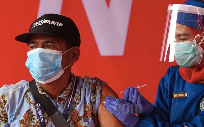 Pekerja sektor transportasi mengikuti vaksinasi massal Covid-19 di terminal Kampung Rambutan, Jakarta, Kamis (10/6/2021). Vaksinasi massal tersebut diperuntukan bagi pelaku transportasi umum dan masyarakat sekitar terminal Kampung Rambutan dengan target sebanyak 1.000 orang. Pemerintah menekankan pentingnya pemberian vaksin Covid-19 kepada pelaku transportasi publik karena memiliki mobilitas dan interaksi yang tinggi dengan masyarakat. Bisnis/Arief Hermawan P