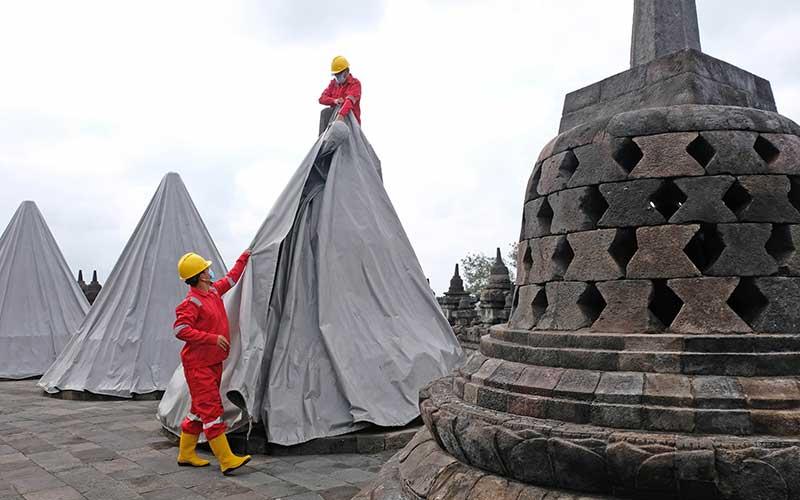 Petugas Balai Konservasi Borobudur (BKB) membuka terpaulin penutup stupa candi Borobudur Magelang, Jawa Tengah, Kamis (10/6/2021). Pembukaan terpaulin yang terpasang sejak bulan November 2020 guna mengantisipasi guyuran abu vulkanik erupsi gunung Merapi tersebut, karena menurut Badan Penyelidikan dan Pengembangan Teknologi Kebencanaan Geologi (BPPTKG) Yogyakarta, Candi Borobudur aman dari ancaman bahaya erupsi Gunung Merapi. ANTARA FOTO/Anis Efizudin