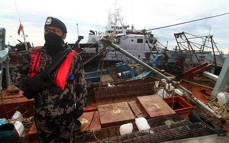Sejumlah petugas Kapal Pengawas Kementerian Kelautan dan Perikanan (KKP) bersiaga di kapal ikan ilegal hasil tangkapan di Stasiun Pengawasan Sumber Daya Kelautan dan Perikanan (PSDKP) Pontianak di Sungai Rengas, Kabupaten Kubu Raya, Kalimantan Barat, Kamis (10/6/2021). Sebanyak 19 kapal ikan ilegal berbendera Malaysia, Vietnam, Filipina dan Indonesia berhasil ditangkap lima kapal pengawas perikanan KKP saat melaksanakan operasi pengawasan di Laut Natuna Utara dan Laut Sulawesi pada 3-8 Juni 2021. ANTARA FOTO/Jessica Helena Wuysang