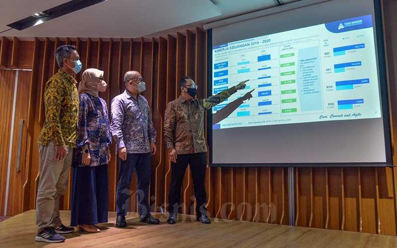 Direktur utama PT Asuransi Jiwa Tugu Mandiri (AJTM) Hanindio W. Hadi (kanan) bersama Direktur Yennita (kedua kiri), Direktur Haris Anwar (kedua kanan), dan Direktur Yuzran Bustamar menunjuk layar yang menampilkan kinerja keuangan PT Asuransi Jiwa Tugu Mandiri (AJTM) di Jakarta, Jumat (11/6). PT Asuransi Jiwa Tugu Mandiri (AJTM) berhasil mebukukan laba setelah pajak sebesar Rp18,39 miliar, meningkat 119 persen dibanding 2019 sebesar Rp8,39 miliar. Sedangkan total aset meningkat 15 persen dari Rp1,7 triliun menjadi Rp1,96 triliun. Bisnis/Fanny Kusumawardhani