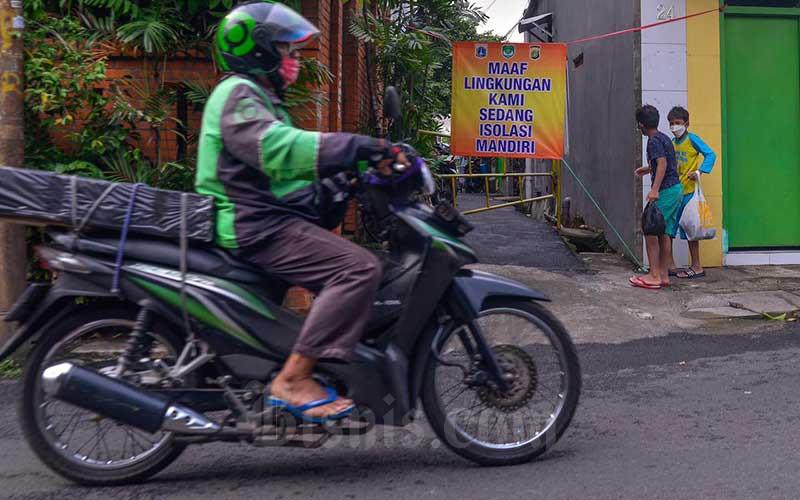 Warga beraktivitas di depan rumah di gang perkampungan yang diberlakukan karantina di RT 007/RW 005, Utan Kayu, Jakarta, Jumat (11/6/2021). Pemberlakuan karantina tersebut dilakukan setelah ditemukan 22 kasus positif Covid-19 dari klaster keluarga. Bisnis/Fanny Kusumawardhani