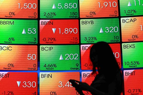 Karyawan berdiri di dekat papan elektronik yang menampilkan pergerakan Indeks Harga Saham Gabungan (IHSG) di Bursa Efek Indonesia, Jakarta. - JIBI/Abdullah Azzam