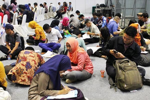 Pencari kerja duduk di lantai saat mengikuti Bursa Kerja Nasional di JIexpo Kemayoran, Jakarta, Jumat (24/3). - Antara/Ade Trilaksono