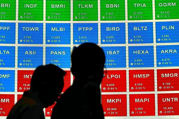 Karyawan berada di dekat papan elektronik yang menampilkan pergerakan Indeks Harga Saham Gabungan (IHSG) di Jakarta. - JIBI/Abdullah Azzam