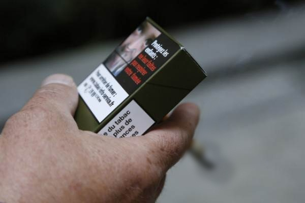 Ilustrasi : Seorang pria memegang kemasan rokok di Paris (25/9/2014) - Istimewa