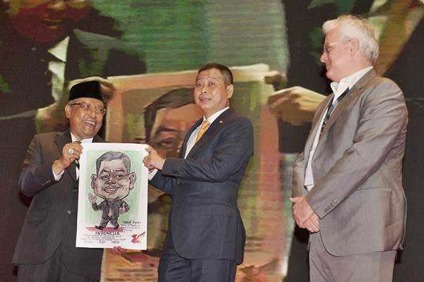 Menteri Energi Sumber Daya Mineral Ignasius Jonan (tengah) memperlihatkan lukisan dirinya bersama Ketua Indonesia Commodity and Derivatives Exchange (ICDX) KH Said Aqil Siroj (kiri) dan CEO ICDX Lamon Rutten pada pembukaan Konferensi Timah Indonesia 2017 di Nusa Dua, Bali, Senin (28/8). - ANTARA/Nyoman Budhiana