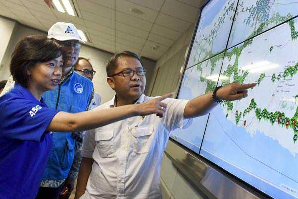 Menkominfo Rudiantara (kanan) bersama Chief Service Management XL Axiata Yessie D. Yosetya (kiri) dan Komisioner BRTI Muhammad Imam Nashiruddin (tengah) melihat layar yang menampilkan jangkauan sinyal XL di jalur mudik saat kunjungan ke Network Monitoring XL di Jakarta, Jumat (23/6). - Antara/Hafidz Mubarak A